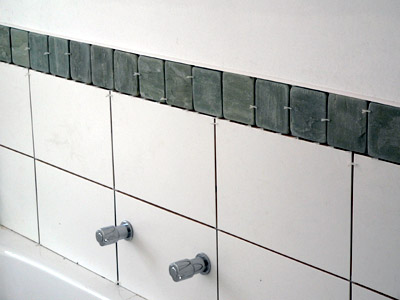 Closeup of master bath tiling and controls