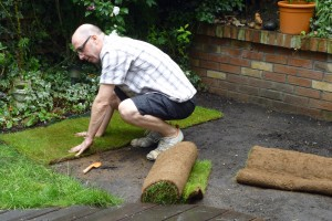 Laying a roll of turf against existing lawn and the edging